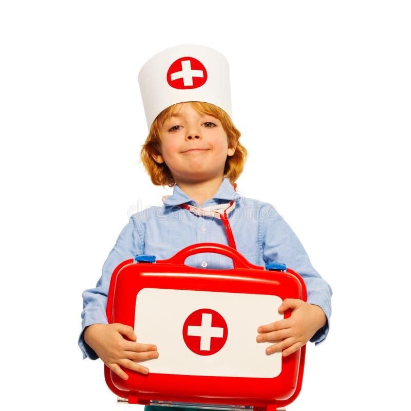 Jeune garçon avec la trousse de premiers soins médicale de chapeau et de jouet photos stock