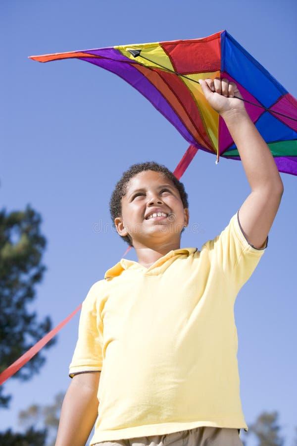 Jeune garçon avec le cerf-volant souriant à l'extérieur photographie stock libre de droits