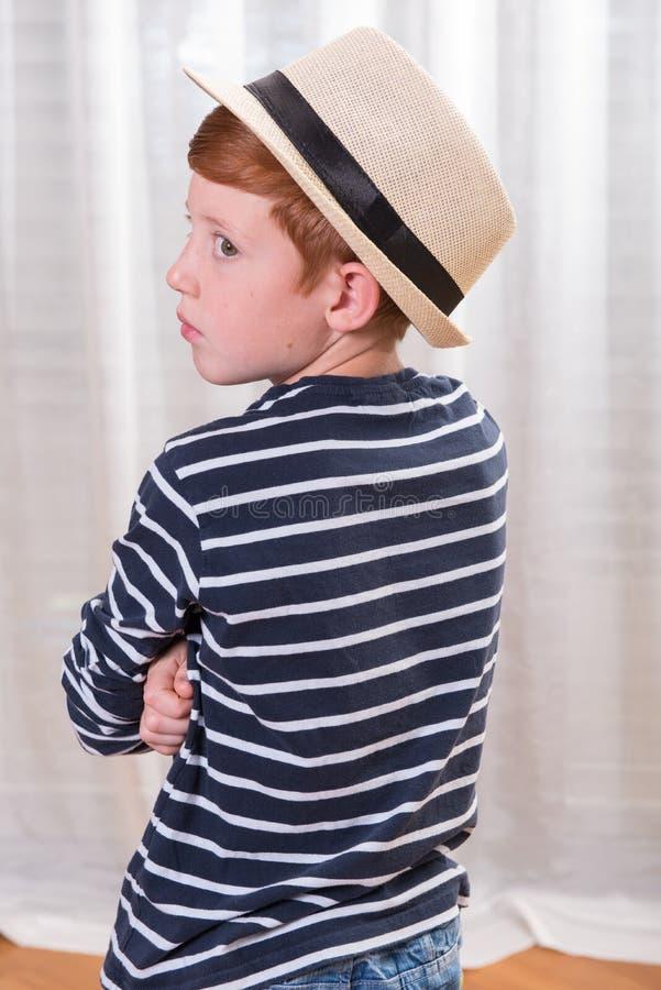 Jeune garçon avec le chapeau regardant au-dessus de son épaule photo libre de droits