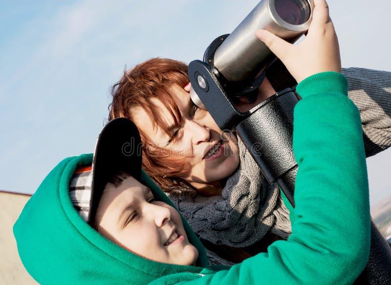 Jeune garçon avec sa grand-mère regardant par un télescope photo stock