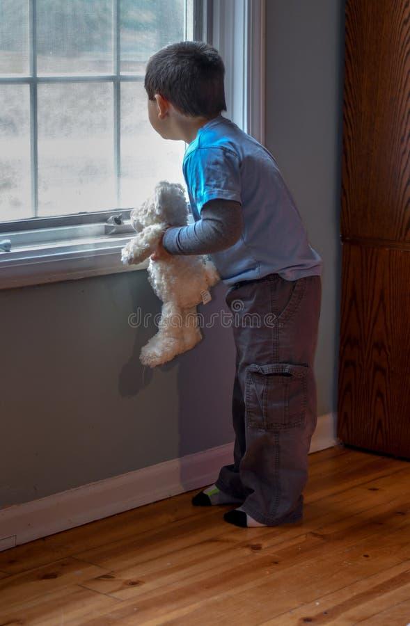 jeune garçon avec son ours bourré, regardant la fenêtre photos stock