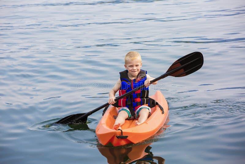 Jeune garçon barbotant un kayak sur un beau lac image libre de droits