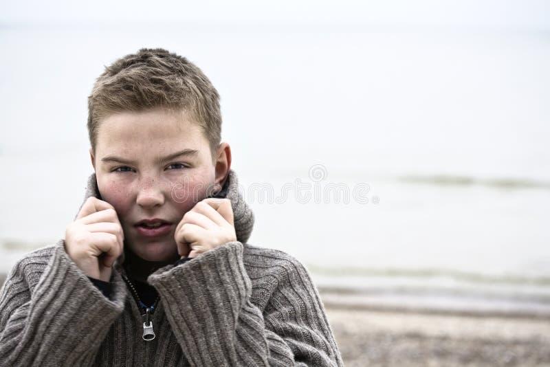 Jeune garçon beau avec le pull à l'hiver de plage images libres de droits