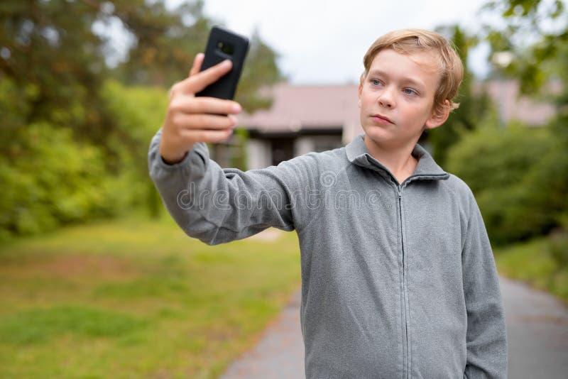 Jeune garçon beau blond prenant Selfie à la maison dehors photos stock