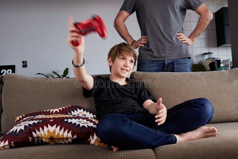 Jeune garçon beau jouant la console de jeu vidéo posée sur un sofa tandis que sa position de père étroite dans le salon à la mais photo libre de droits