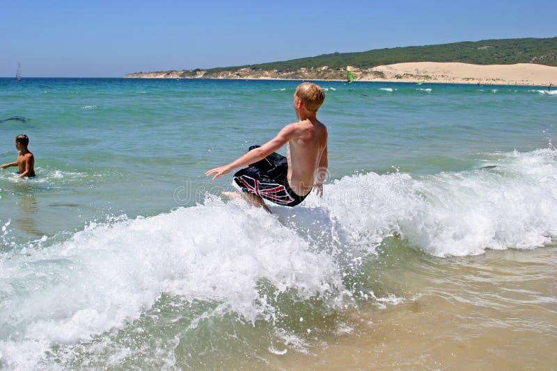 Jeune garçon branchant dans l'onde sur une plage ensoleillée photographie stock libre de droits