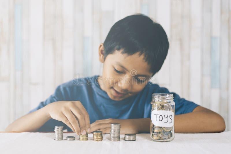 Jeune garçon comptant ses pièces de monnaie/épargne pour acheter les jouets rêveurs photo stock