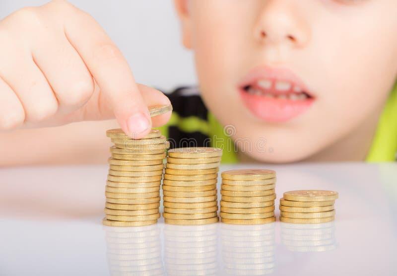 Jeune garçon comptant ses pièces de monnaie images libres de droits