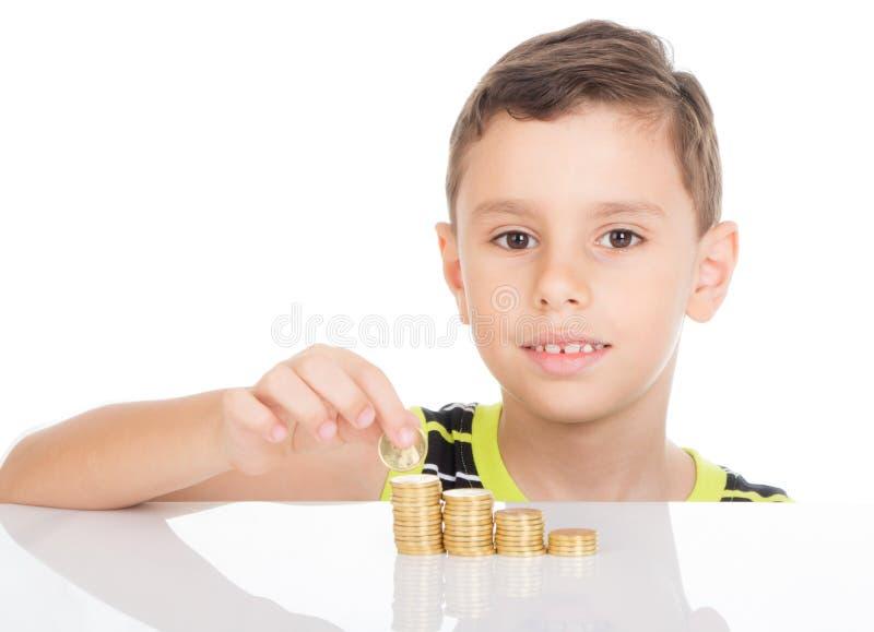 Jeune garçon comptant ses pièces de monnaie photographie stock libre de droits