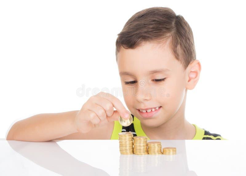 Jeune garçon comptant ses pièces de monnaie photographie stock