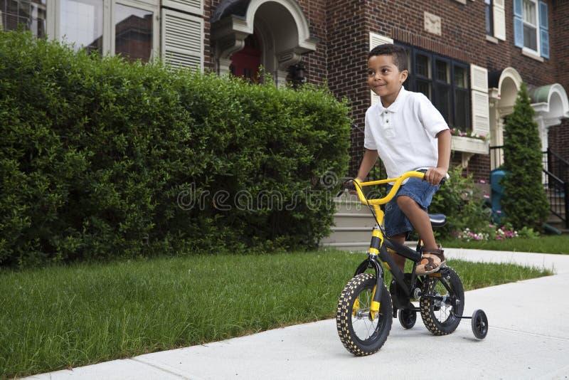 Jeune garçon conduisant sa bicyclette photo stock