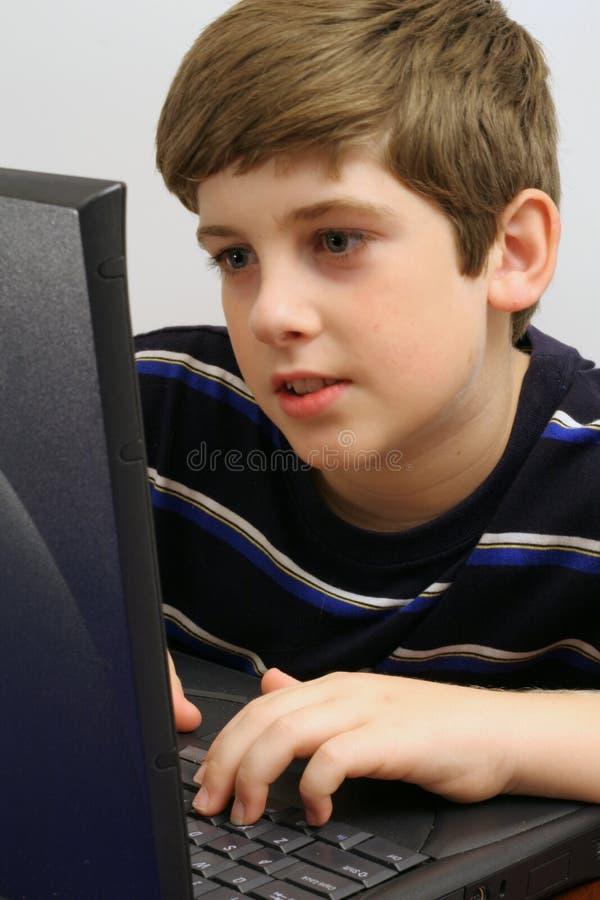 Jeune garçon contrôlant la verticale d'email photo stock