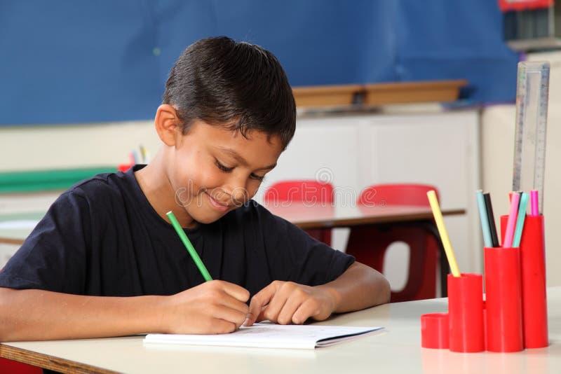 Jeune garçon d'école 10 écrivant à son bureau de salle de classe photo libre de droits