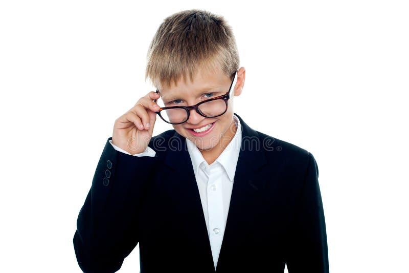 Jeune garçon d'affaires regardant par ses glaces image stock