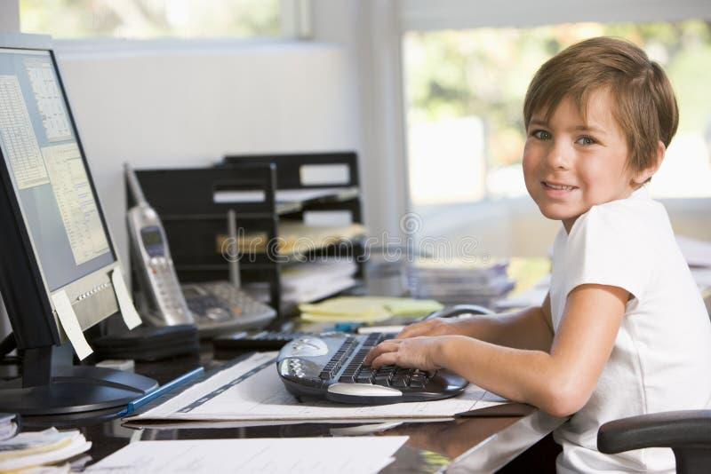 Jeune garçon dans le Home Office avec l'ordinateur images stock