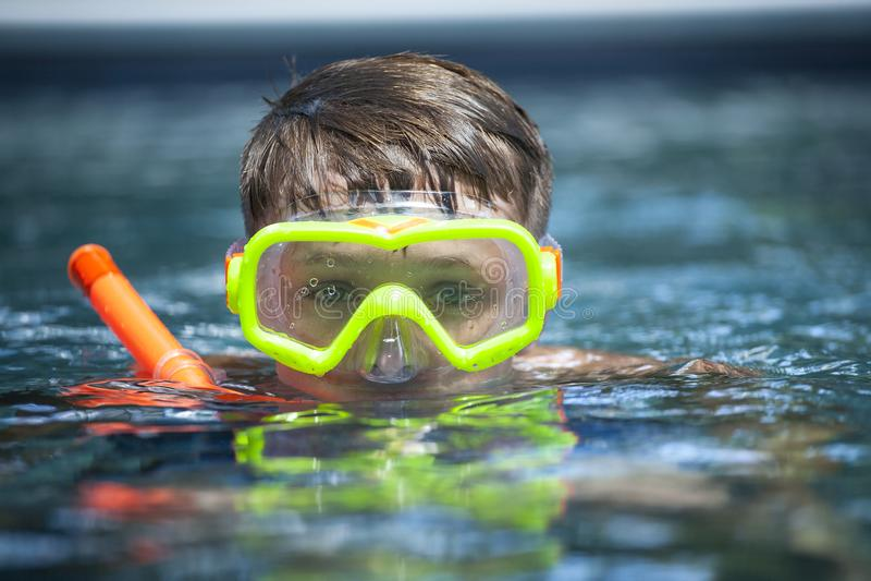 Jeune garçon dans une piscine avec un masque de prise d'air images libres de droits