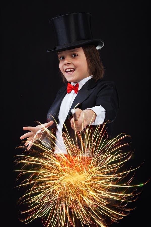 Jeune garçon de magicien à l'aide de sa baguette magique magique photos stock