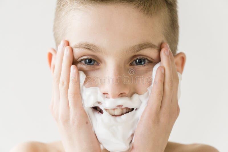 Jeune garçon de sourire appliquant la crème à raser au visage photographie stock libre de droits