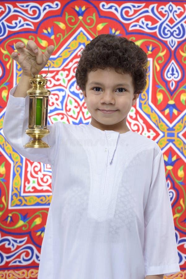 Jeune garçon de sourire avec la lanterne célébrant Ramadan images stock