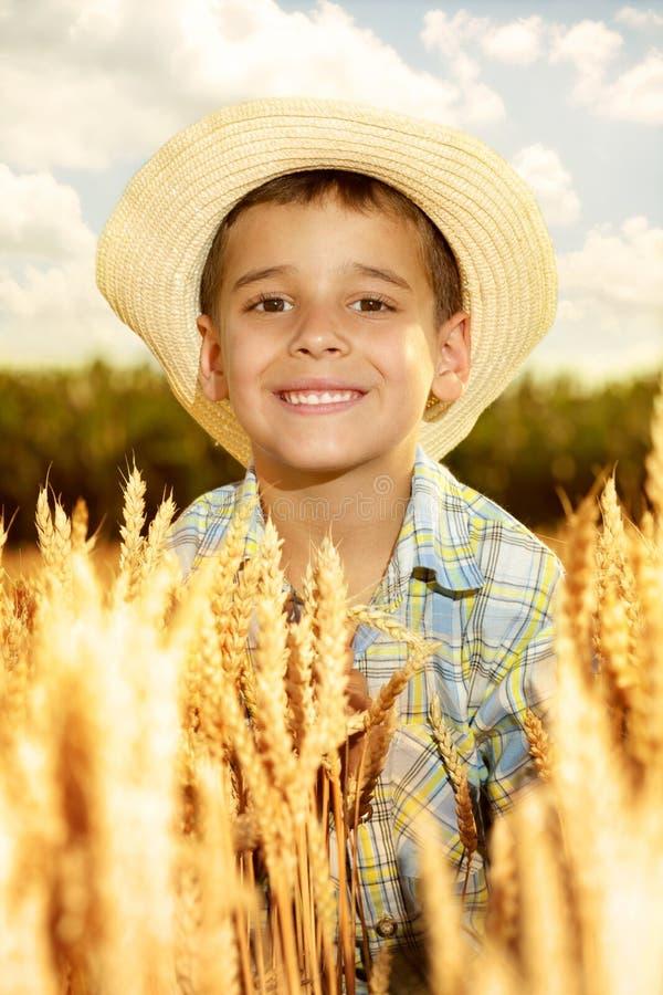 jeune garçon de sourire avec le chapeau de paille dans un domaine de whe photos stock