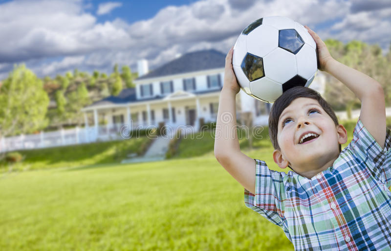 Jeune garçon de sourire tenant le ballon de football devant la Chambre photo libre de droits