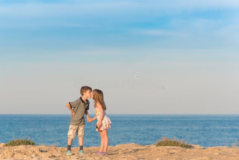 Jeune garçon embrassant une fille photo stock