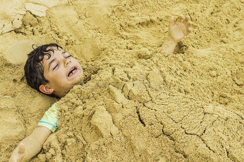 Jeune garçon enterré en sable photo stock