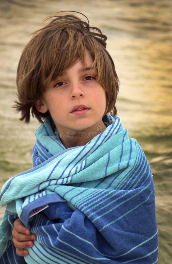 Jeune garçon enveloppé à la plage images libres de droits