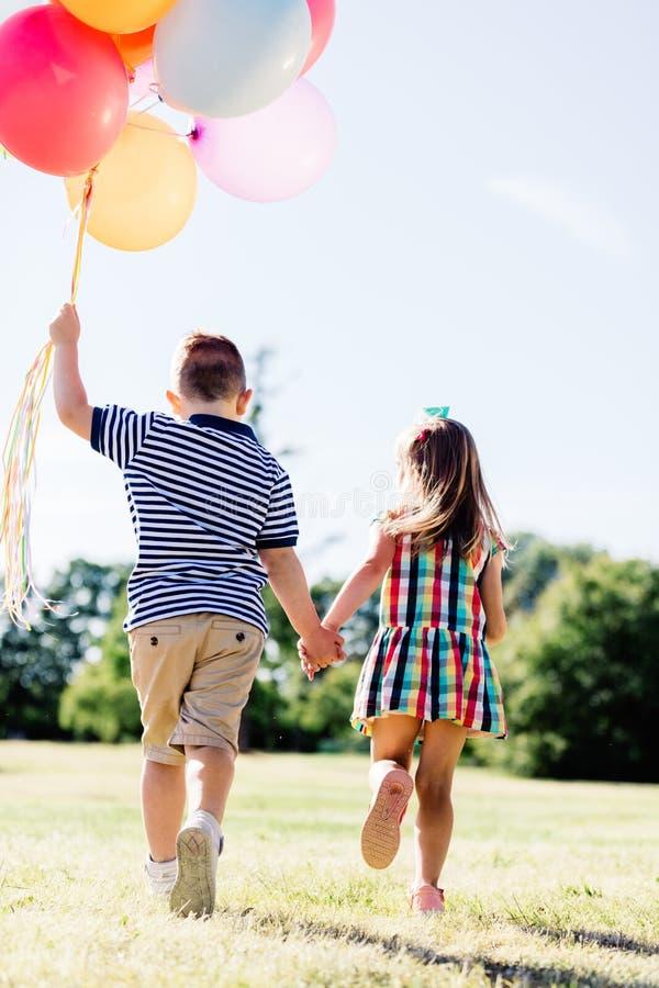 Jeune garçon et une fille courant avec un groupe de ballons colorés photos stock