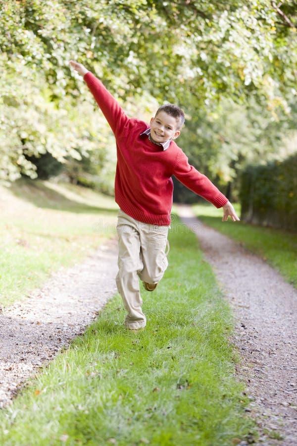 Jeune garçon exécutant sur un chemin souriant à l'extérieur images stock