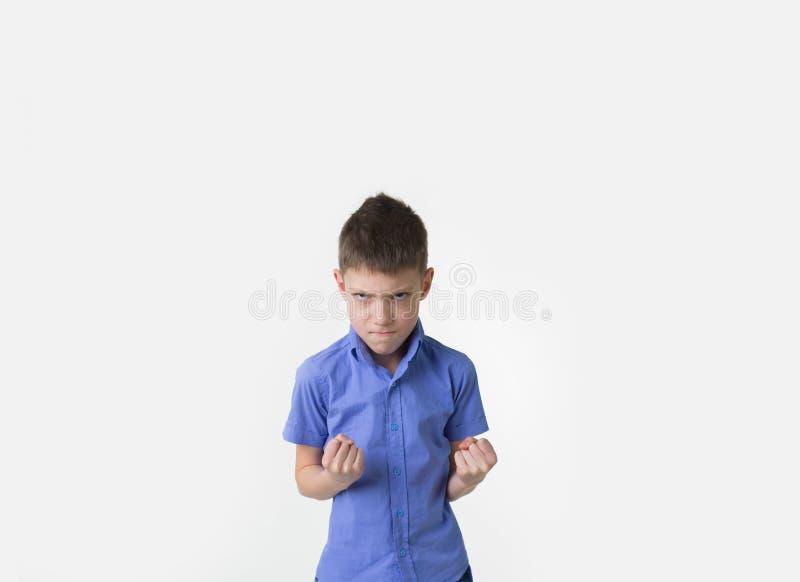 Jeune garçon fâché avec des poings serrés d'isolement sur le blanc image libre de droits