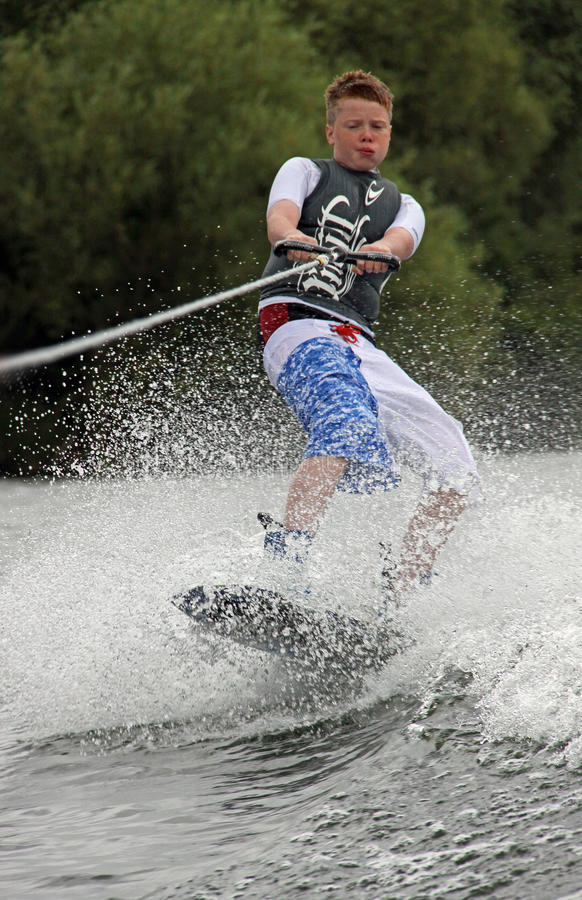 Jeune garçon faisant wakeboarding/surfant image stock