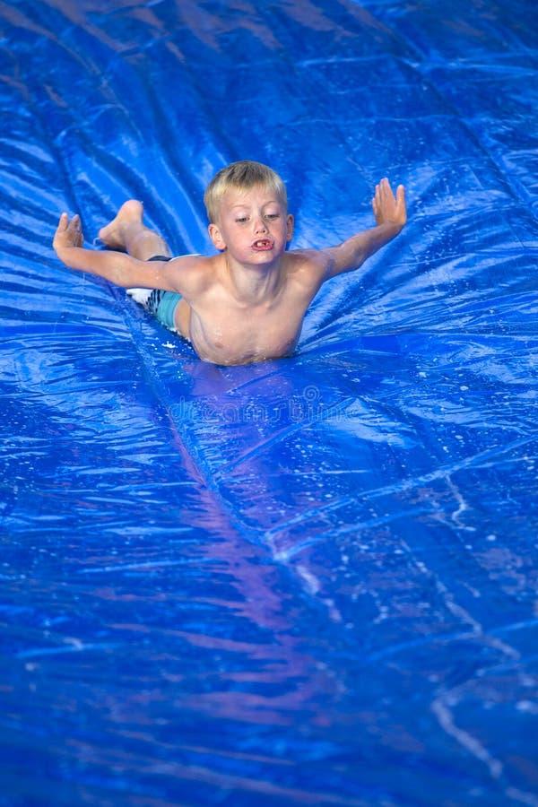 Jeune garçon glissant vers le bas un glissement et une glissière dehors image libre de droits
