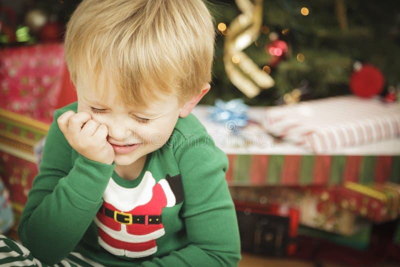Jeune garçon grincheux s'asseyant près de l'arbre de Noël photos stock