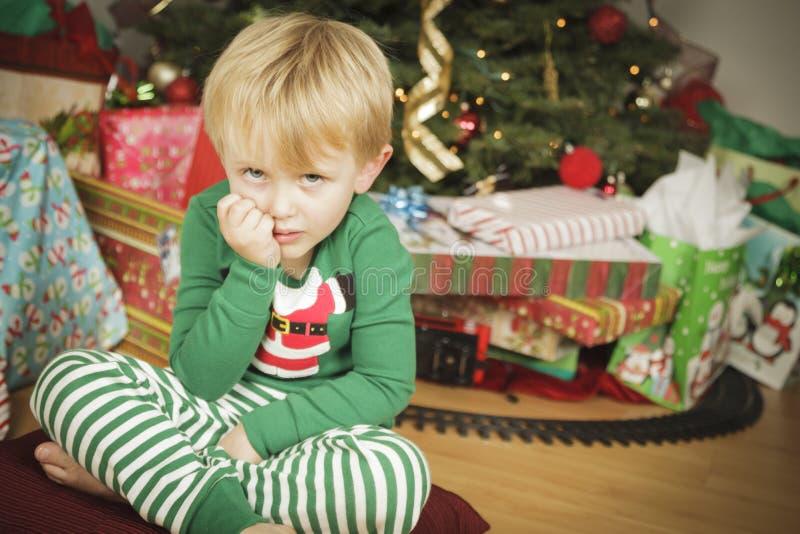 Jeune garçon grincheux s'asseyant près de l'arbre de Noël photo libre de droits