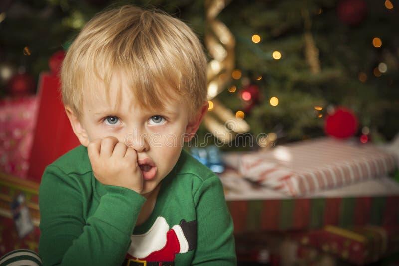 Jeune garçon grincheux s'asseyant près de l'arbre de Noël photo stock