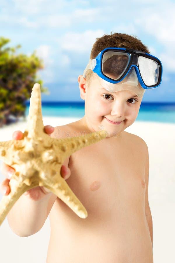 Jeune garçon heureux ayant l'amusement sur la plage tropicale images stock