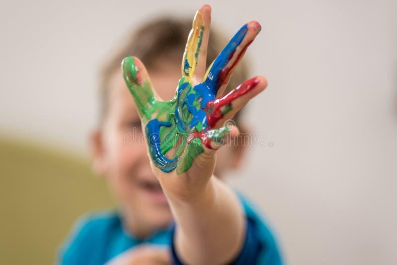 Jeune garçon heureux faisant la peinture de main image stock