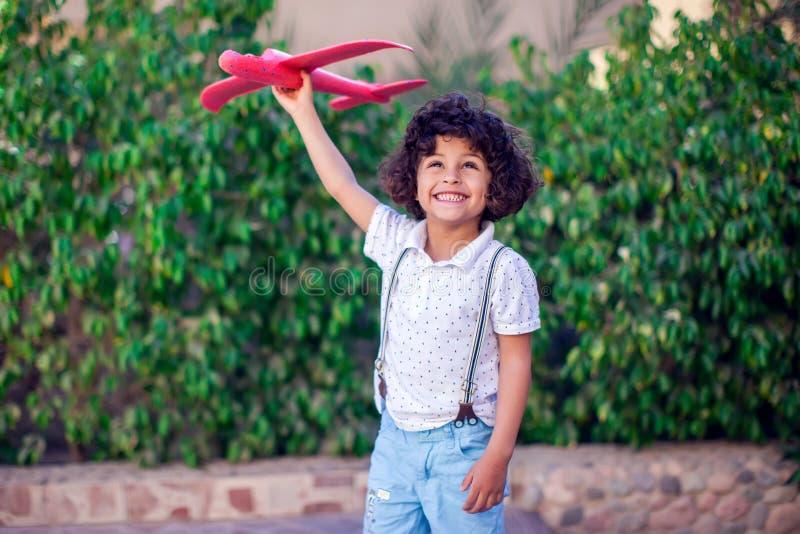 Jeune garçon heureux jouant avec l'avion rouge extérieur photographie stock