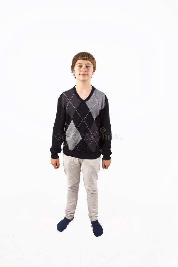 Jeune garçon heureux posant dans le studio images stock