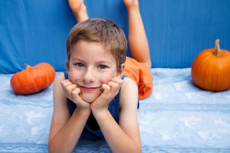 Jeune garçon heureux se couchant sur le fond bleu avec des potirons images stock