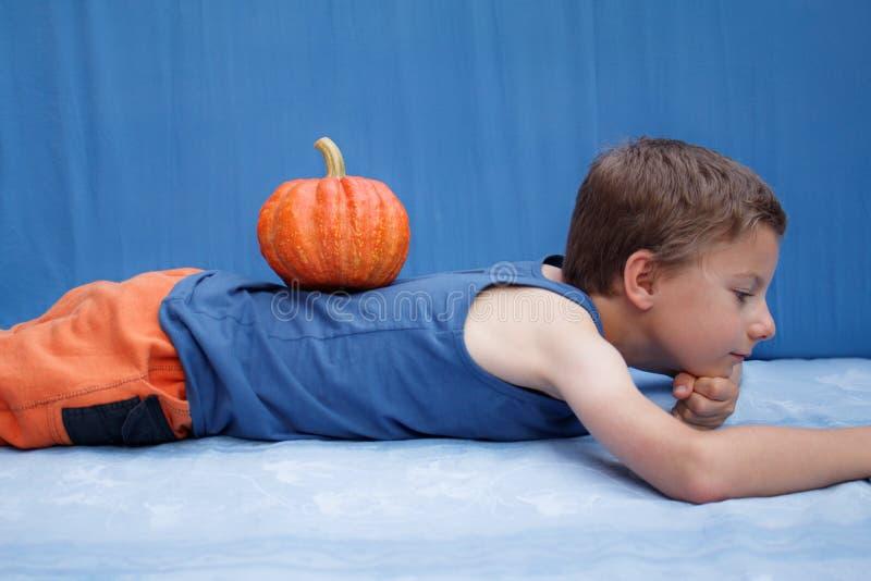 Jeune garçon heureux se couchant sur le fond bleu avec le potiron images libres de droits