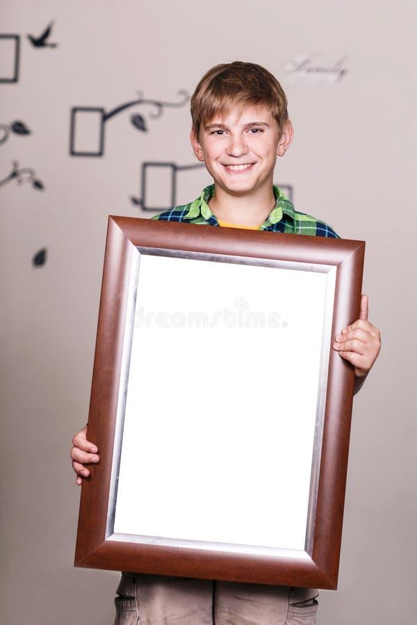 Jeune garçon heureux tenant le cadre de portrait image libre de droits