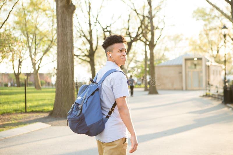 Jeune garçon hispanique avec la promenade de packpack sur le campus d'université image stock
