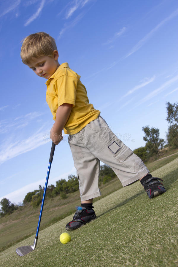 Jeune garçon jouant au golf images libres de droits