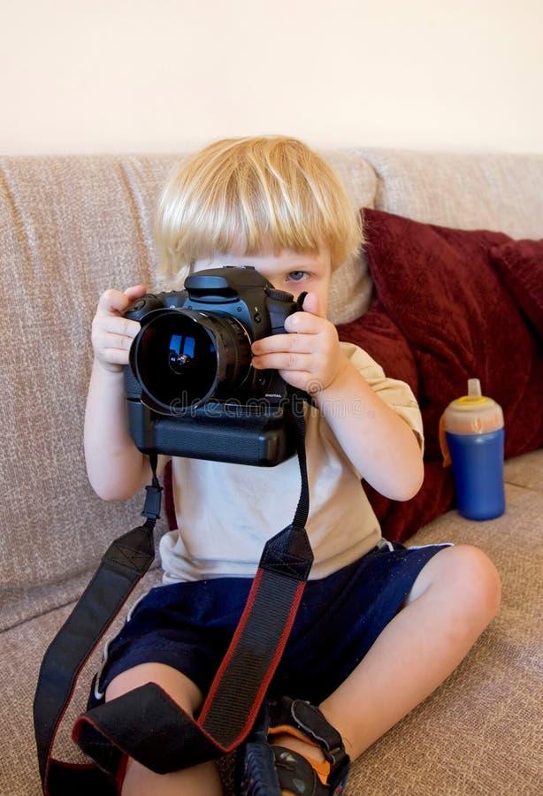 Jeune garçon jouant avec l'appareil photo numérique de SLR image libre de droits