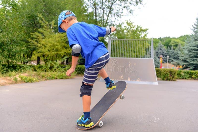 Jeune garçon jouant avec sa planche à roulettes photos libres de droits