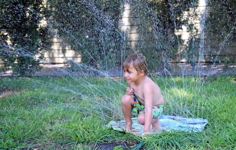 Jeune garçon jouant dans une arroseuse de pelouse photos libres de droits