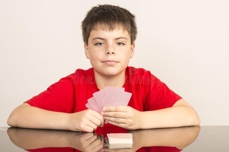 Jeune garçon jouant des cartes photos stock