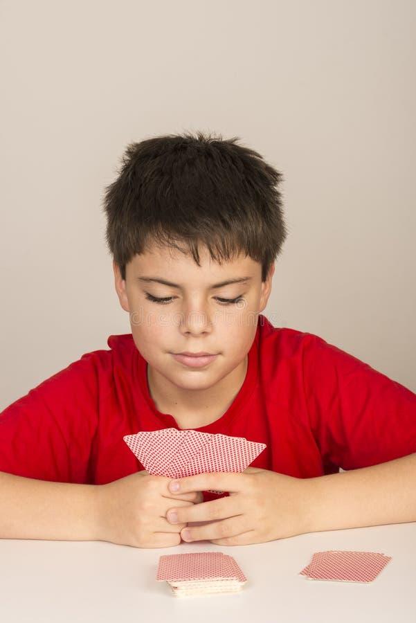 Jeune garçon jouant des cartes images stock